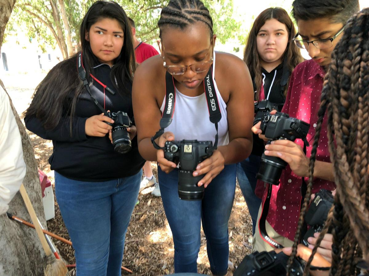 (From left) Dara Garcia, Ivory Bacy, Stephany Rocha and Rohan Patel take photos of the snake.