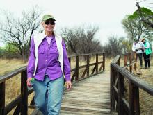 Prof. Carol Schwalbe walks on bridge at refuge.