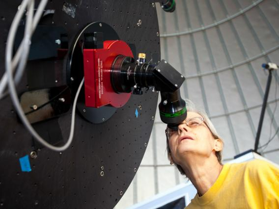 Prof. Carol Schwalbe looks through a telescope.