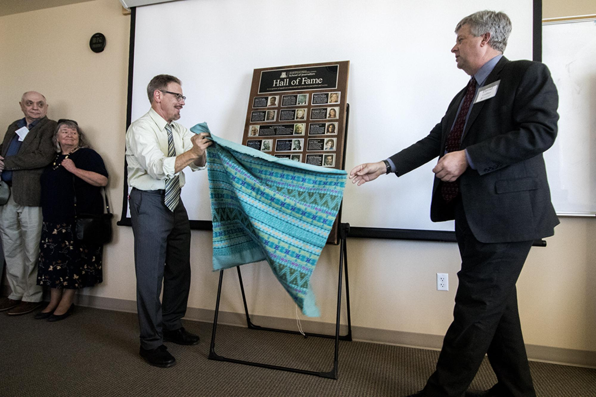 Director David Cuillier and Mike Chesnick, outreach coordinator, unveil the school's Hall of Fame plaque.