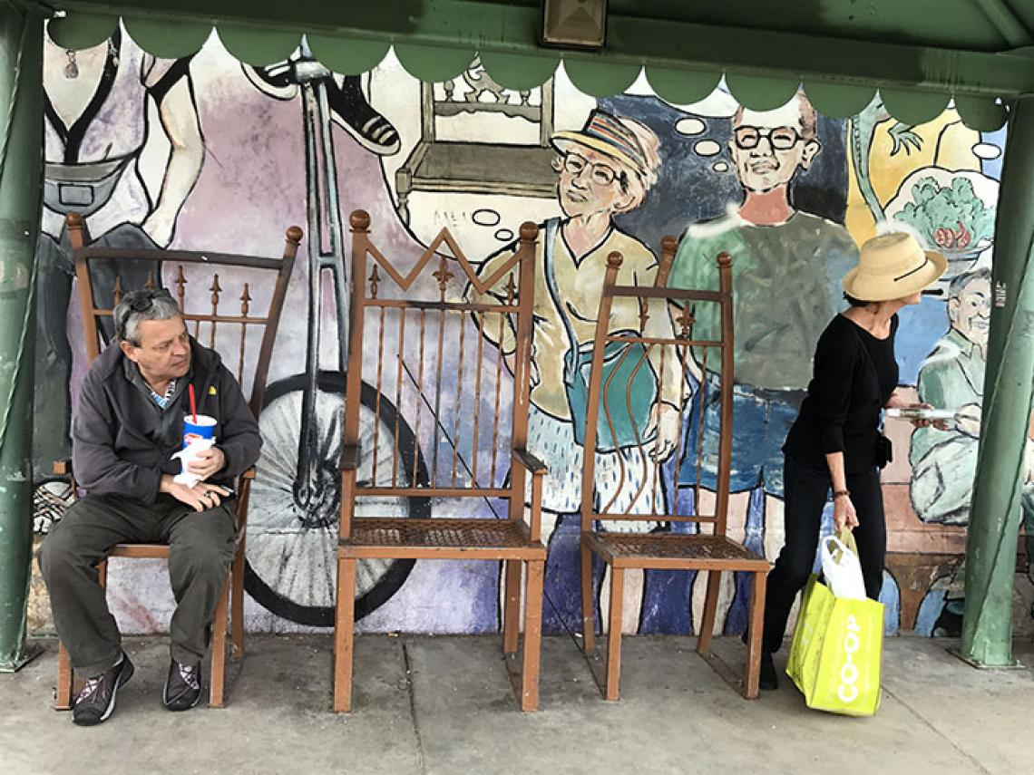 people siting in front on mural