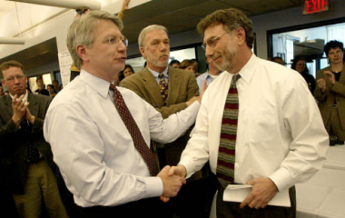 Richard Gilman congratulates then-editor Marty Baron after The Boston Globe won the 2003 Pulitzer Prize for Public Service.